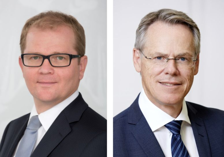 "The picture shows portraits of the two Managing Directors of the Austrian Treasury. The left side of the picture shows the Managing Director of the division ""Markets"", Markus Stix. He wears thick black glasses and a dark blue suit, a white shirt and a light blue tie. The right side of the picture shows the Managing Director of the division ""Risk Management & Operations"", Walter Joestl. He wears a dark blue suit, a white shirt and a dark blue-striped tie as well as frameless glasses."
